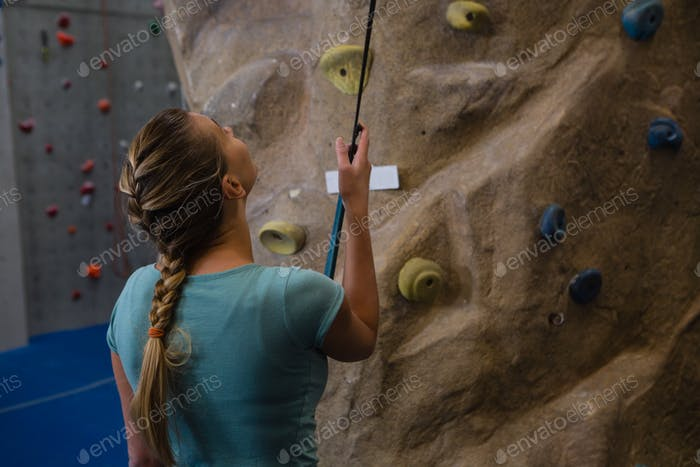 Rear view of athlete standing by climbing wall with rope in fitness studio