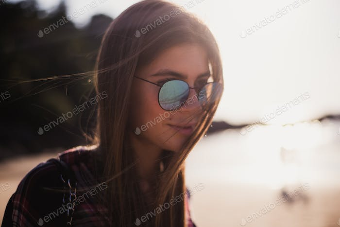 Close up beach portrait of cheerful blonde hipster. Wild girl on summer beach with sunglasses