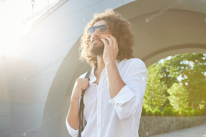 Outdoor shot of handsome pretty bearded male with curls talking on mobile phone