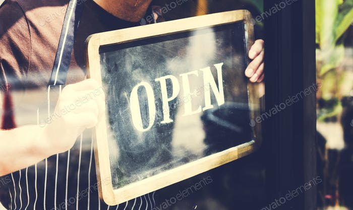 Man putting on shop open sign