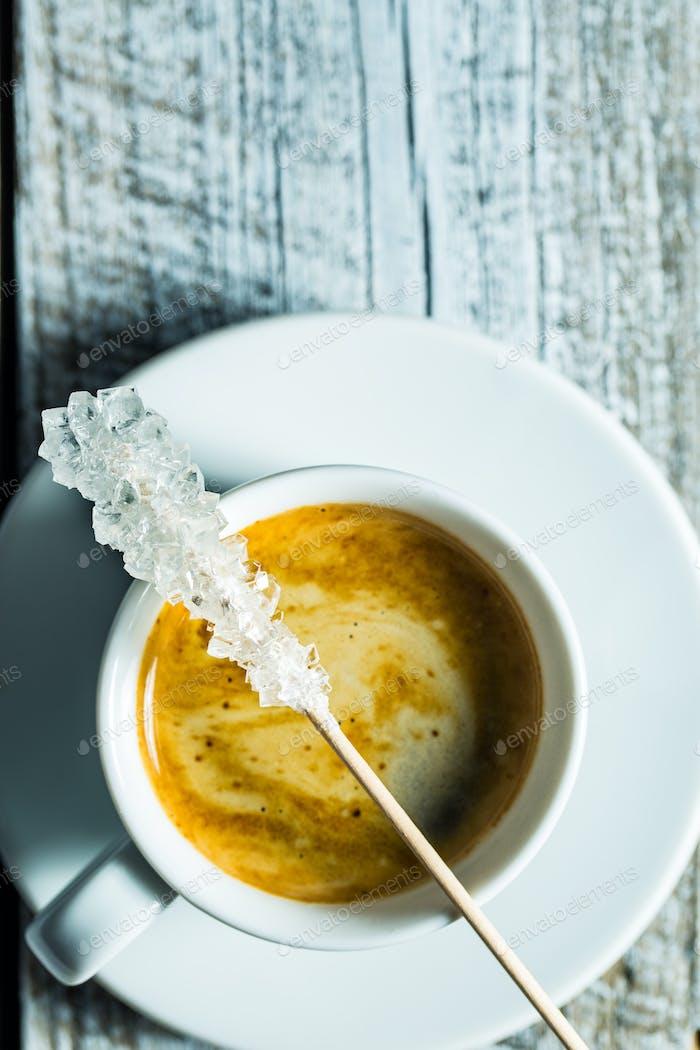 Kristallisierter Zucker auf Holzstab und Kaffeetasse.