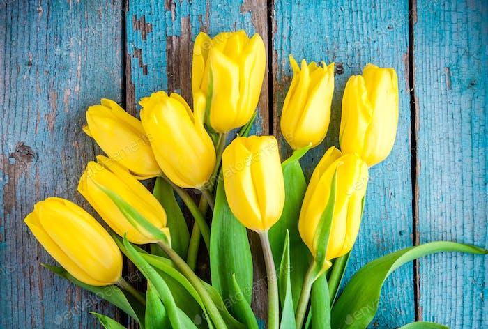 Blumenstrauß von gelben Tulpen auf einem blauen rustikalen Hintergrund