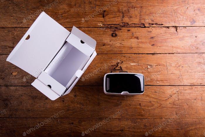 Virtual Reality Brille mit Papierschachtel auf Holztisch