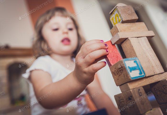 Mädchen spielen mit Bausteinen auf dem Boden