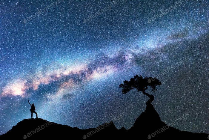 Milky Way, silhouette of woman and tree. Space