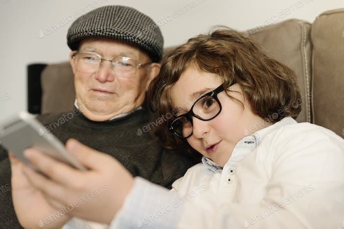 Grandfather and grandson are taking selfie.