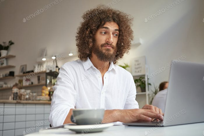 Indoor portrait of puzzled bearded young male working remotely with laptop, looking at screen