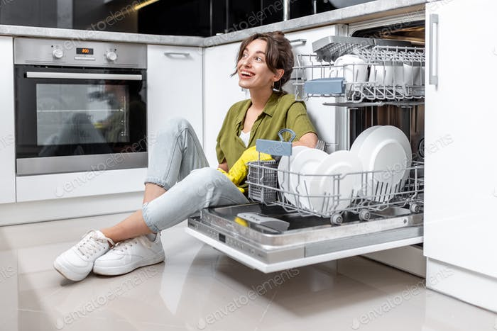 Housewife near the dishwasher at home