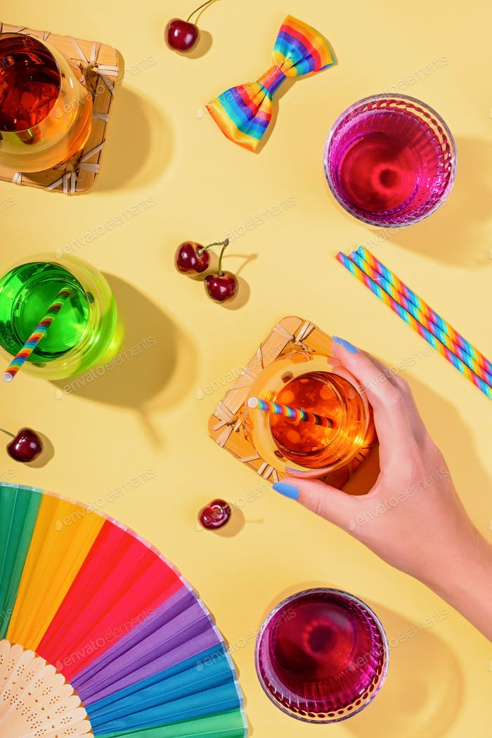 Colorful cocktails on yellow table for rainbow party with rainbow drinking straws