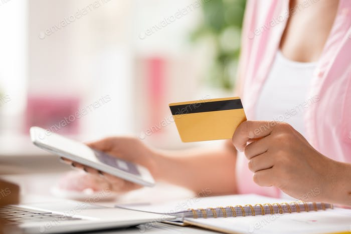 Young female online shopper with smartphone using plastic card to pay for order