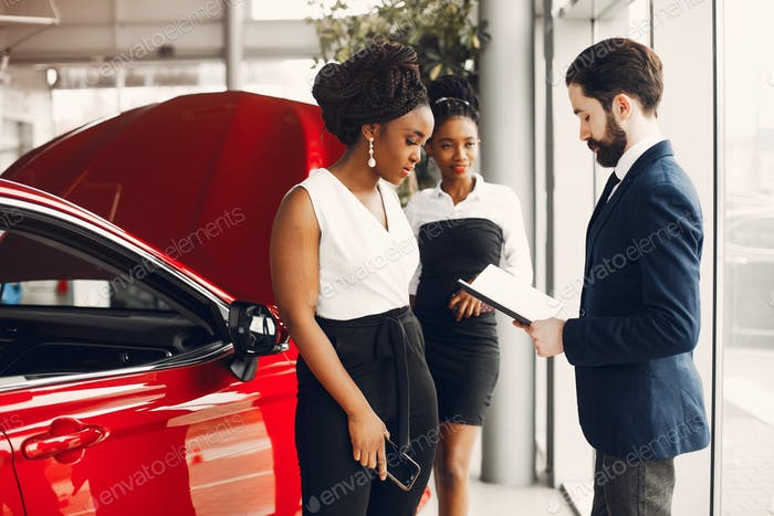 Two stylish black woman in a car salon