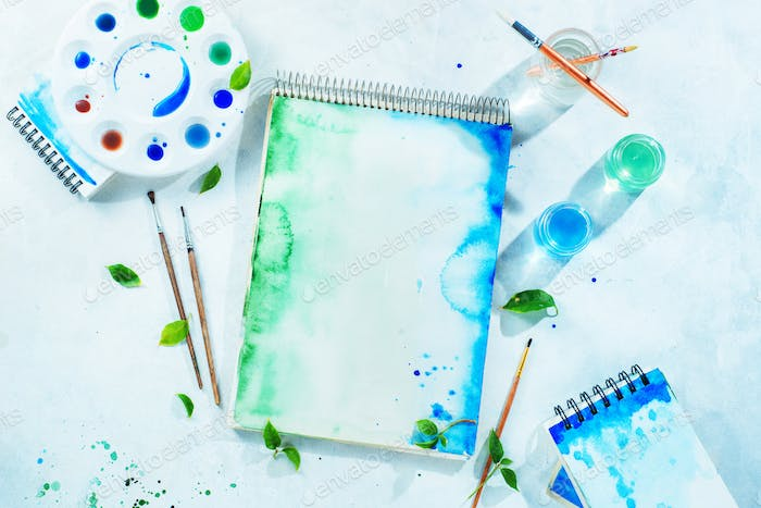 Drawing spring concept with artist tools, green and blue watercolor sketchbooks, brushes and color