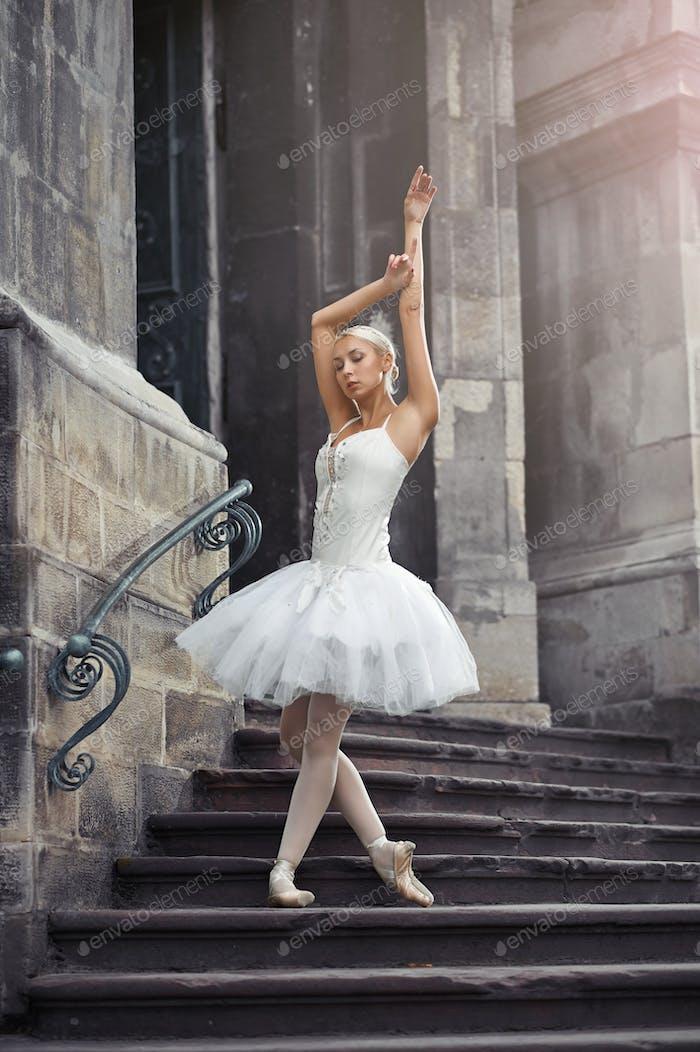 Beautiful ballerina dancing near an old building