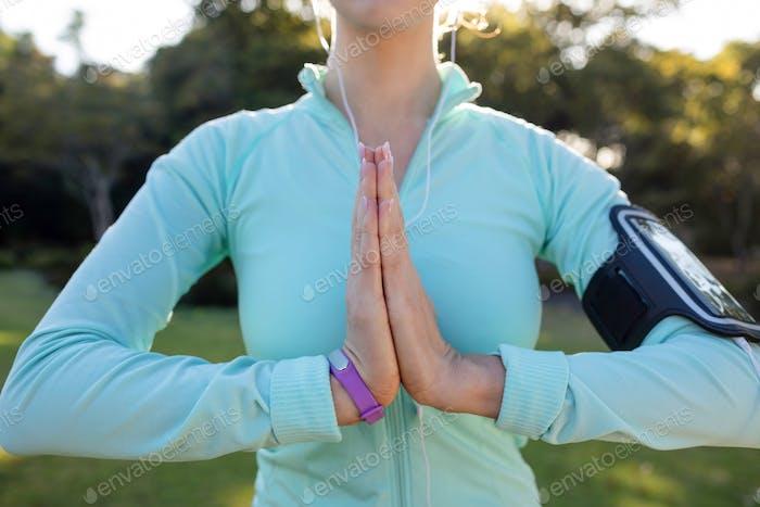 Mittlerer Teil der weiblichen Jogger Musik hören und trainieren mit den Händen Gelenk