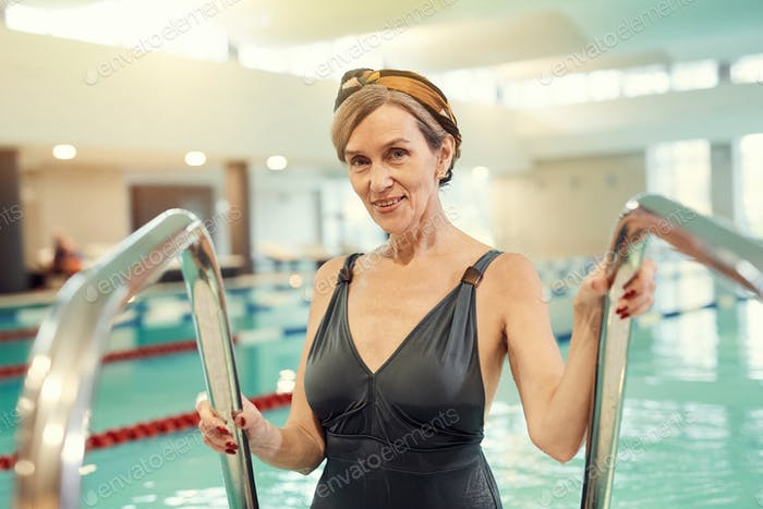 Smiling Mature Woman Entering Swimming Pool