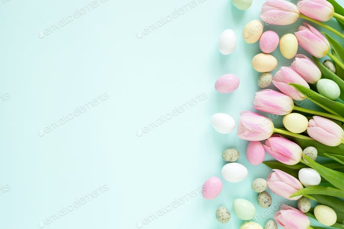Easter Colorful Candy Eggs and Pink Tulips on Turquoise Background.