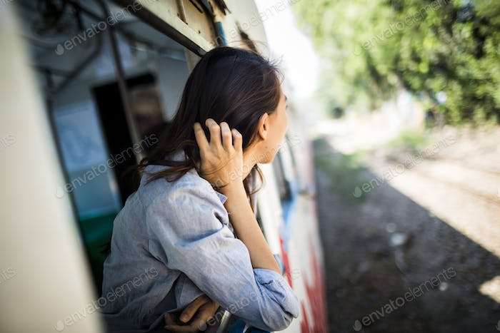 Young woman riding on a train, looking out of window.