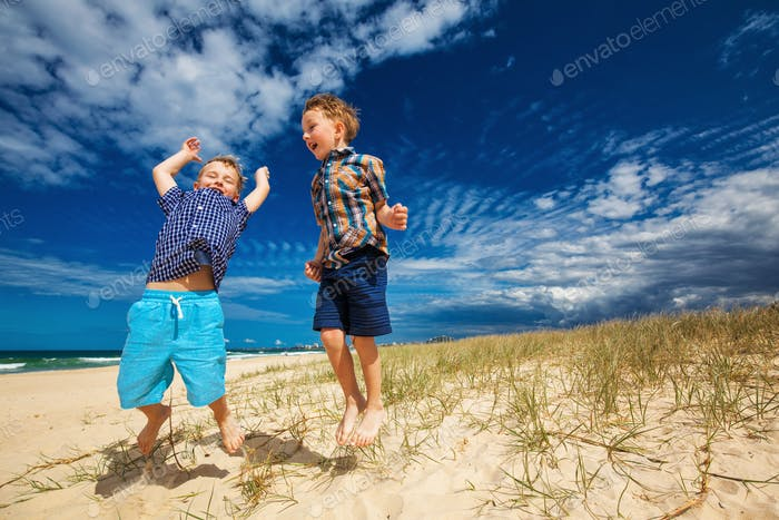 Young happy boys having fun on tropical beach, jumping into the