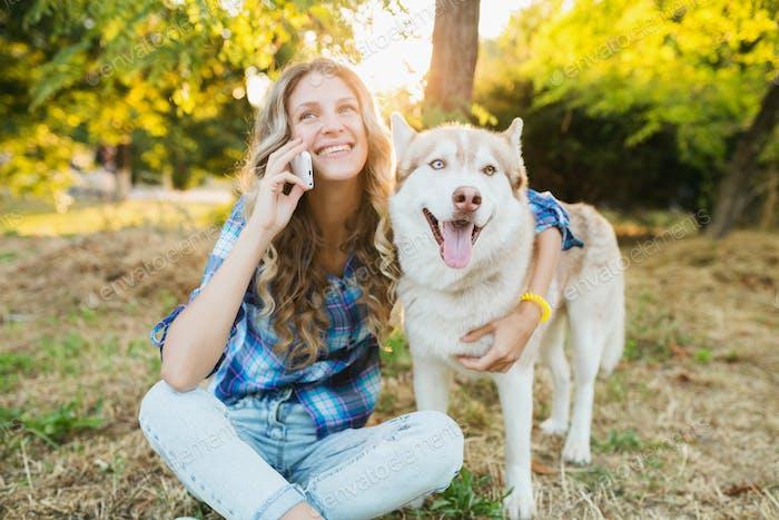mujer con perro hablando por teléfono