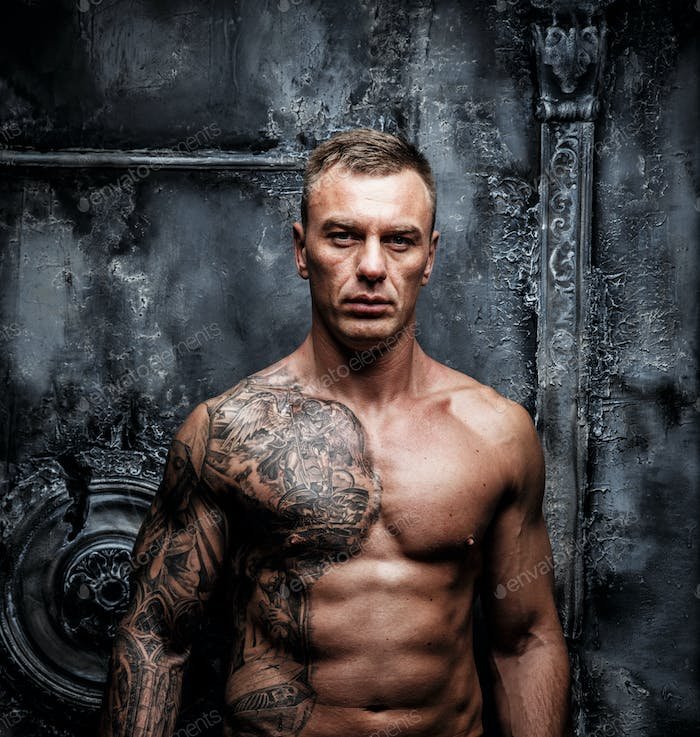 Portrait of muscular male with tattoo.
