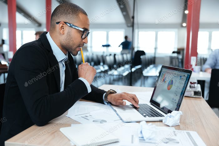 Concentrated businessman looking at laptop