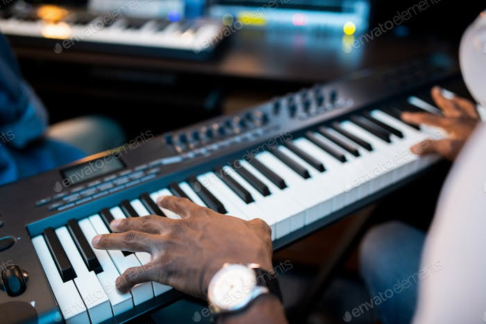Hands of young African composers or musician touching keys of pianoboard