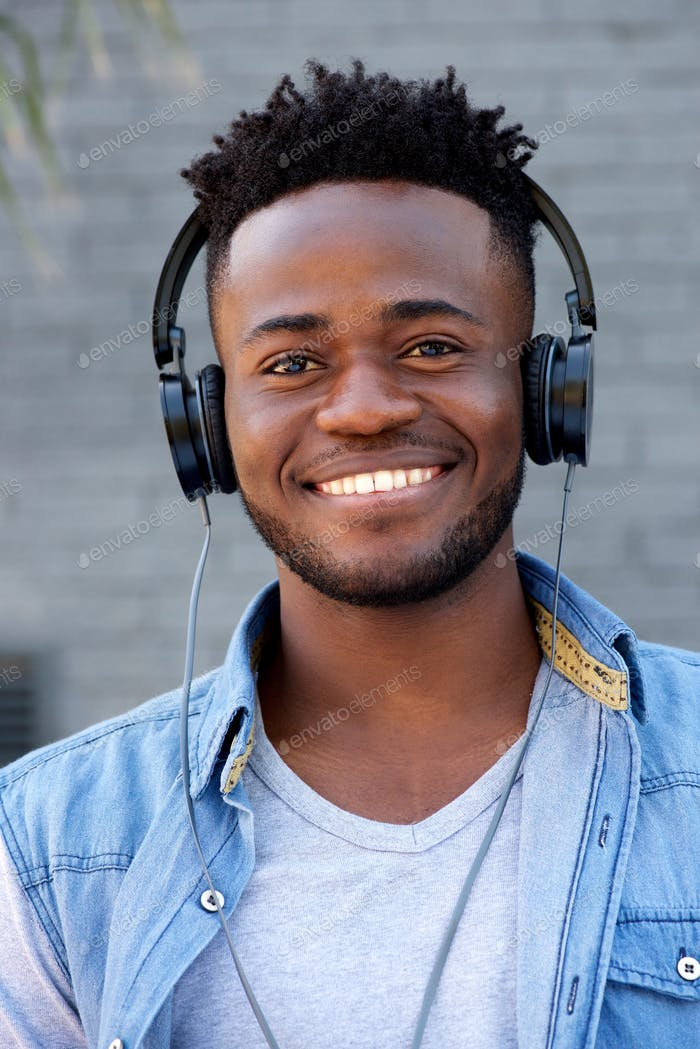 Close up cool young black guy listening to music with headphones