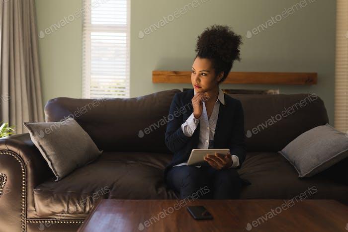 Female real estate agent using digital tablet on sofa in living room