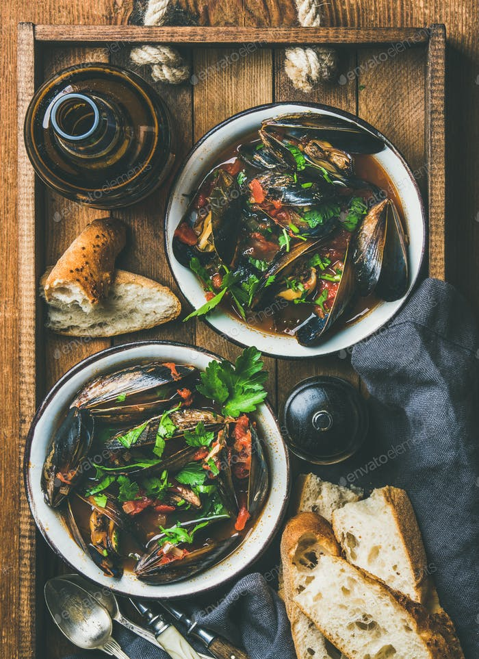 Flat-lay of boiled mussels in tomato sauce and light beer