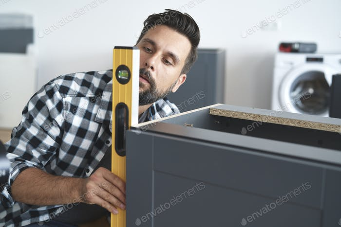 Carpenter checking the furniture levels using a spirit level