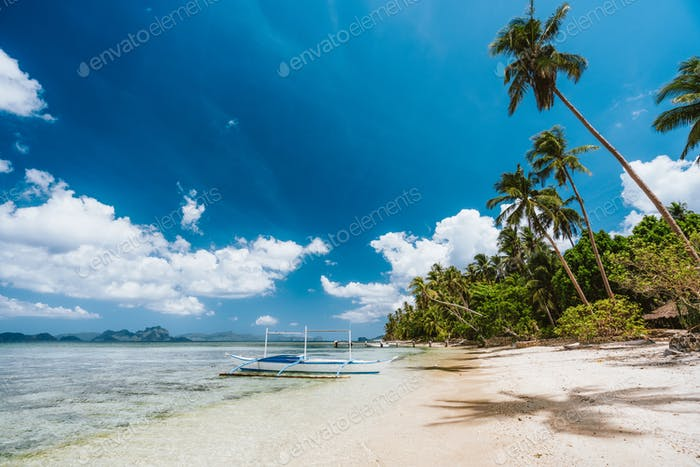 El Nido, Palawan, Philippines. Sandy beach with palm trees, tourist boat and blue sky