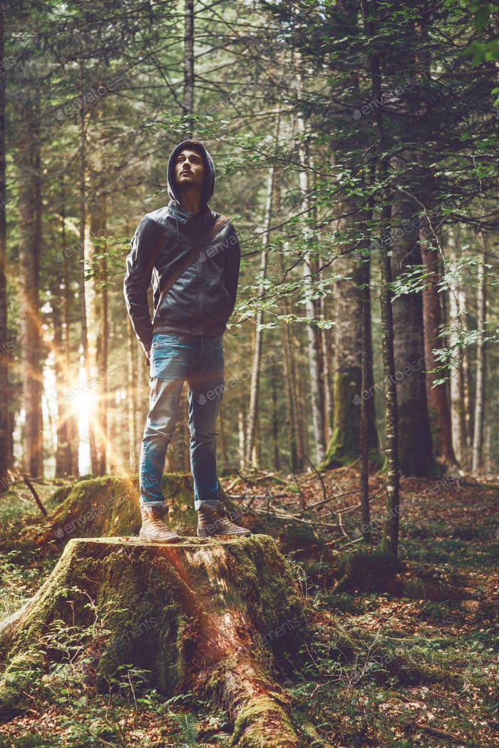 Confident man standing in the forest