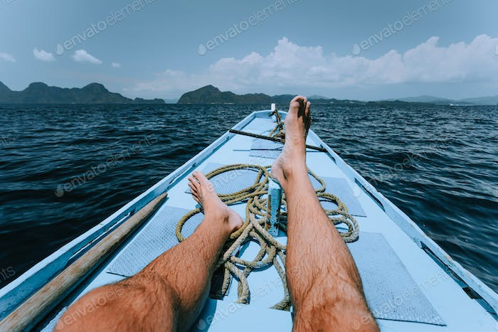 Legs of man on banca boat approaching tropical island. travel, summer exotic vacation holidays