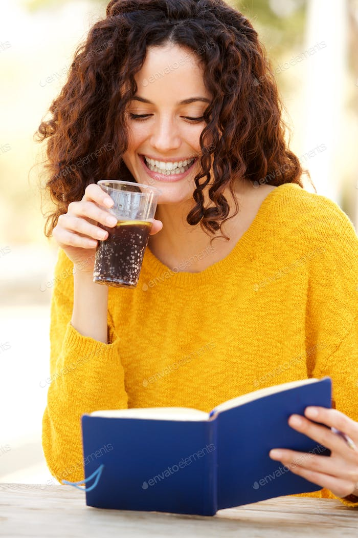 young woman reading book with a drink