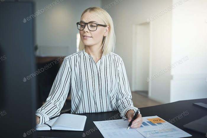 Smiling businesswoman working at her desk in a bright office