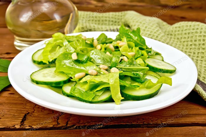 Salad from spinach and cucumber with napkin on board