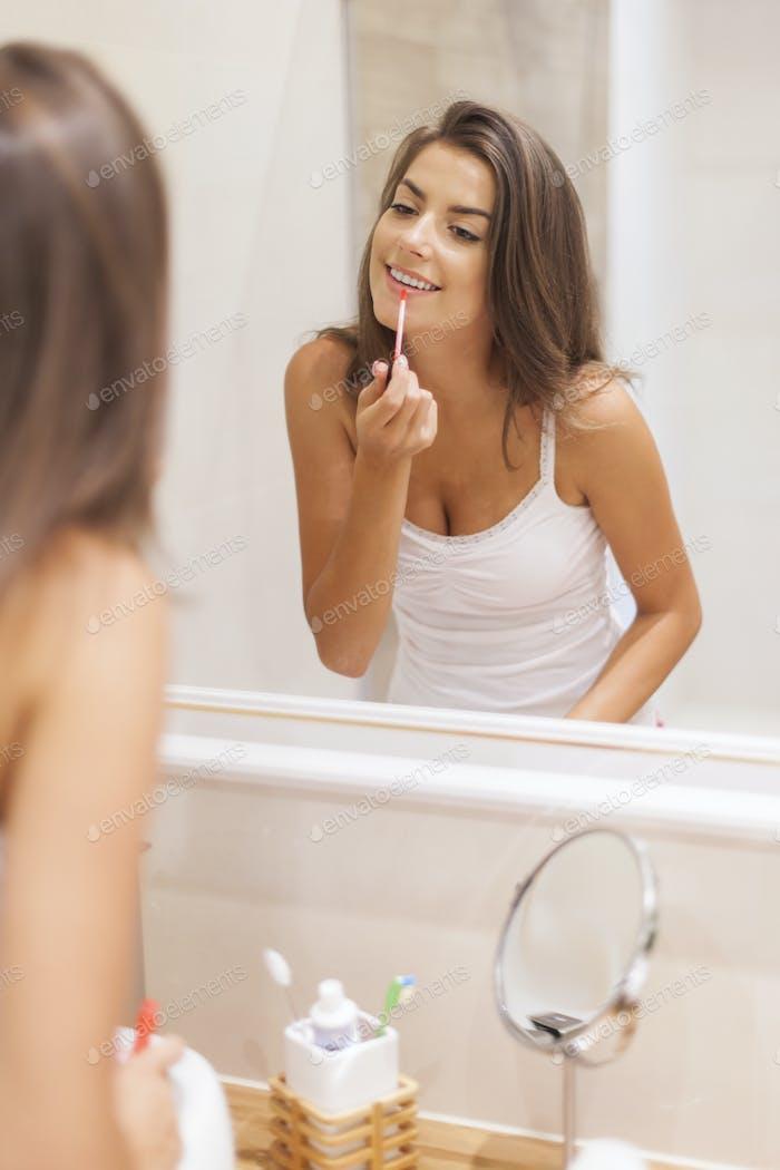 Beautiful woman applying lip gloss in bathroom