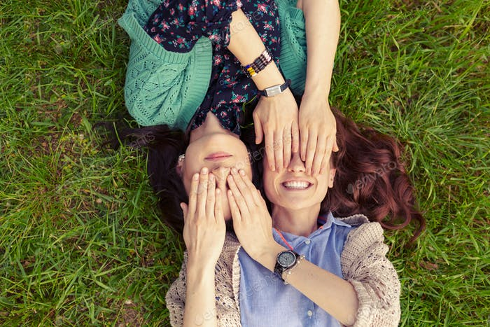 Top view of smiling friends lying on grass having fun