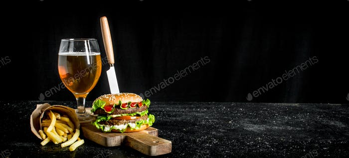 Burger with a knife,fries, beer in a glass.