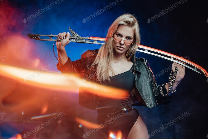 Sexy female soldier with sword poses in background with radiance