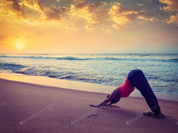 Young sporty fit woman doing yoga at beach on sunset