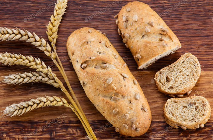 oaf of bread, bread slices and wheat over wooden background