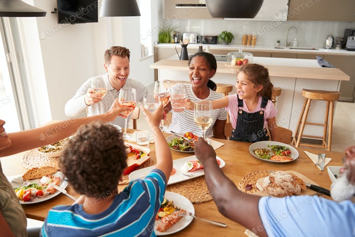 Multi-Generation Mixed Race Family Making A Toast Before Eating Meal Around Table At Home Together