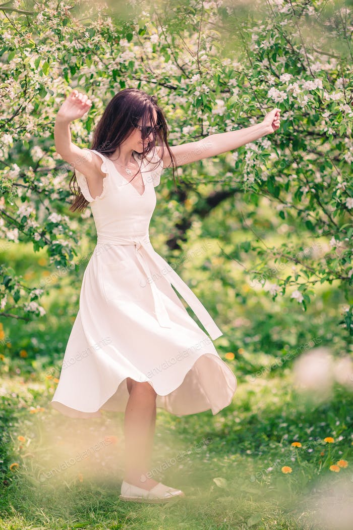 Beautiful woman enjoying smell in spring cherry garden