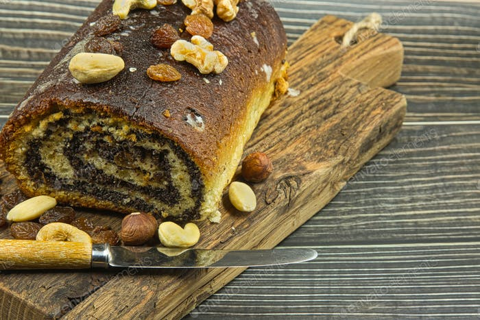 Poppy seed cake with raisins and nuts on an old chopping board