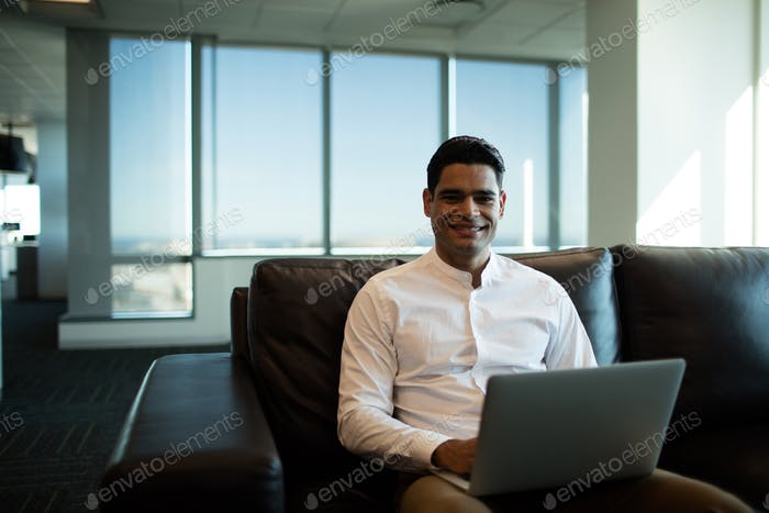 Businessman using laptop while sitting of sofa in office