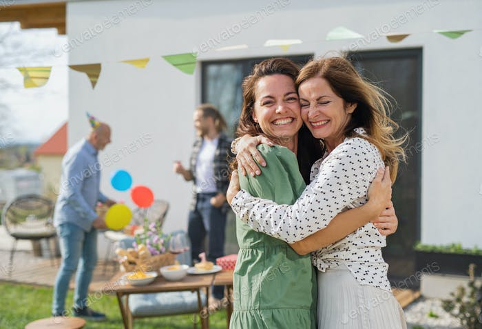 Young woman with mother outdoors in garden at home, birthday celebration party