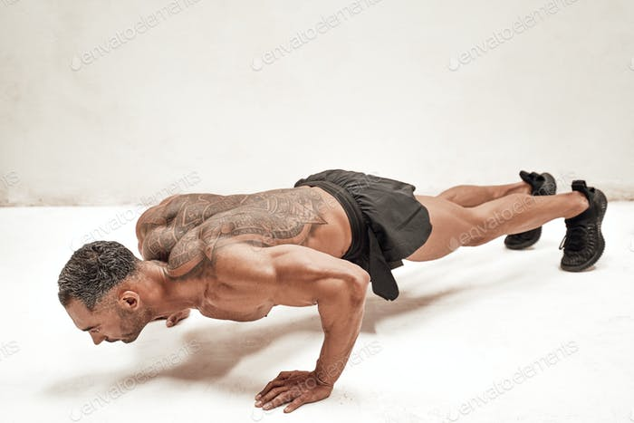 Healthy and energetic man doing plank exercises, focused and looking strong