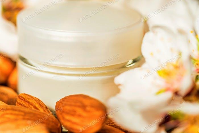 Mandeln, Gesichtscreme und weiße Blüten