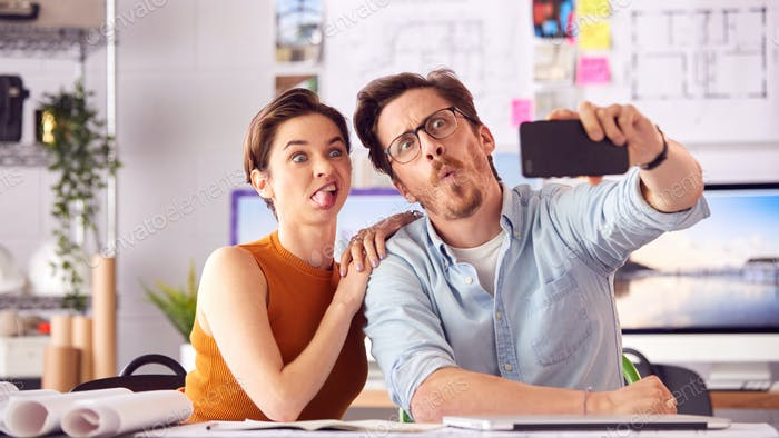 Male And Female Architects In Office Posing For Selfie And Pulling Funny Faces Together